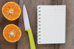 Mandarin oranges and acrylic knife placed on the old wooden floo Stock Images
