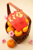 Mandarin oranges in basket with Chinese New Year red packets Royalty Free Stock Image