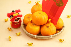 Mandarin oranges in basket with Chinese New year red packets and lion doll - Series 3 Royalty Free Stock Image
