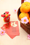 Mandarin oranges in basket with Chinese New year red packets and mini lion doll - Series 4 Stock Photo