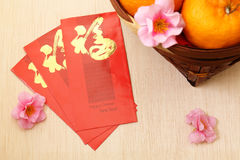 Mandarin oranges in basket with Chinese New Year red packets - Series 3 Royalty Free Stock Image