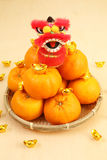 Mandarin oranges in basket with mini lion doll Royalty Free Stock Photos