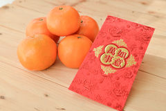 Mandarin oranges with Chinese new year red packets  (Foreign tex. T means All achievements &#x29 Royalty Free Stock Images