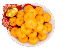 Mandarin oranges,  gold nuggets, red packets with good luck char Royalty Free Stock Image