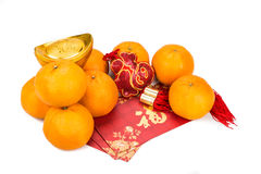 Mandarin oranges, gold nuggets, red packets with good luck chara Royalty Free Stock Photography