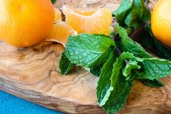 Mandarin oranges and mint. Leaves on a beautiful olive wood board Royalty Free Stock Image