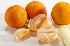 Mandarin oranges. One of the open with some fresh slices on a wooden white table Royalty Free Stock Image