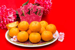 Mandarin oranges and red packets with Chinese Good Luck character. Mandarin oranges on plate with Good Luck festive greetings Chinese character on red packets stock image