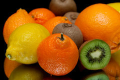 Mandarin and other fruits closeup on black background Stock Images