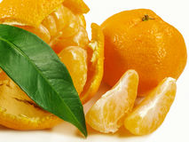 Mandarin, peeled mandarin with slices and green leaf. Royalty Free Stock Photography