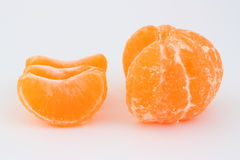 Mandarin. Peeled mandarin with three separated slices on a white Stock Photo