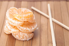 Mandarin roll and chopsticks. On wooden background Royalty Free Stock Photo