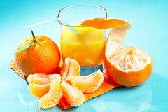 Mandarin and sinas juice. Mandarins and fresh orange juice on blue stock photo