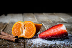 Mandarin, strawberry on an old wooden table in an Stock Photos