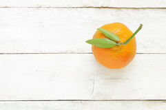 A mandarin on a white wooden table Royalty Free Stock Photos