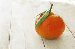 A mandarin on a white wooden table Royalty Free Stock Image