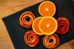 Mandarin wordt gediend op een donkere steen met een decor van een schilcitrusvrucht Een halve mandarijn en een schil van spiraal  stock foto