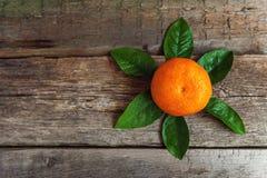 Mandarina con las hojas en fondo de madera Imágenes de archivo libres de regalías