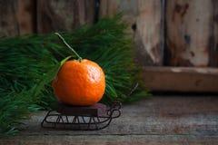 Mandarina de la Navidad en los trineos del vintage con las ramas del árbol de abeto en el fondo de madera Fotos de archivo