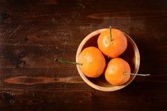 Mandarina en un cuenco de madera en la tabla de madera oscura Foto de archivo libre de regalías