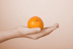 Mandarina en una palma de los niños imagenes de archivo