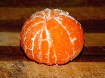 Mandarina pelada en una tajadera de madera Imagen de archivo