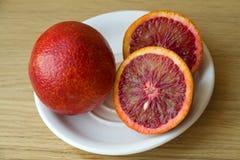 Mandarina roja en una placa blanca Imagenes de archivo