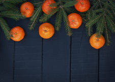 Mandarinas anaranjadas con las ramas spruce en un backgro de madera negro Imágenes de archivo libres de regalías