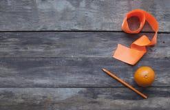 Mandarinas con el lápiz y la cinta anaranjada en viejo ingenio de madera de la tabla Fotos de archivo