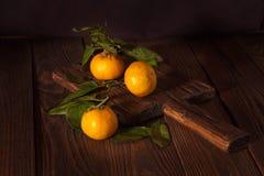 Mandarinas con las hojas, concepto oscuro de la Navidad del fondo en vagos de madera Foto de archivo libre de regalías