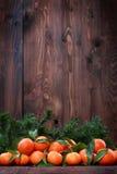 Mandarinas con las hojas en superficie de madera Foto de archivo