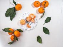 Mandarinas con las hojas en una tabla blanca, tablero decorativo de la Navidad fotos de archivo