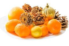 Mandarinas, conos, bolas de la Navidad en una placa blanca Fotografía de archivo libre de regalías