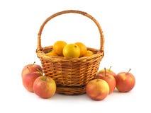 Mandarinas en cesta de mimbre y manzanas cerca aisladas Fotos de archivo