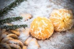 Mandarinas en la nieve en una tabla de madera, Año Nuevo, una vida inmóvil Fotos de archivo
