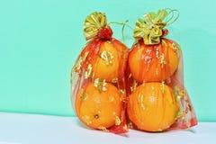 Mandarinas en los bolsos netos rojos por Año Nuevo chino Imagen de archivo libre de regalías