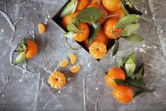 Mandarinas frescas con las hojas en la cesta de acero en piedra gris Foto de archivo
