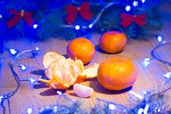 Mandarinas maduras, Año Nuevo/árbol de navidad con los arcos del rojo y guirnalda azul en la plantilla de madera del fondo Foto de archivo