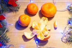 Mandarinas maduras, Año Nuevo/árbol de navidad con los arcos del rojo y guirnalda azul en la plantilla de madera del fondo Fotos de archivo