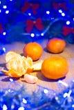 Mandarinas maduras, Año Nuevo/árbol de navidad con los arcos del rojo y guirnalda azul en la plantilla de madera del fondo Imágenes de archivo libres de regalías