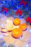 Mandarinas maduras, Año Nuevo/árbol de navidad con los arcos del rojo y guirnalda azul en la plantilla de madera del fondo Imagen de archivo