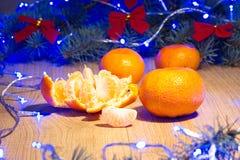 Mandarinas maduras, Año Nuevo/árbol de navidad con los arcos del rojo y guirnalda azul en la plantilla de madera del fondo Imagenes de archivo