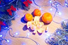 Mandarinas maduras, Año Nuevo/árbol de navidad con los arcos del rojo y guirnalda azul en la plantilla de madera del fondo Fotografía de archivo libre de regalías