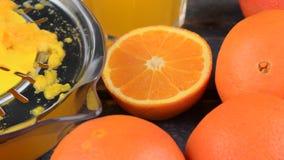 Mandarinas, naranjas, un vidrio de zumo de naranja y squezeer manual de la fruta cítrica en fondo de madera azul Naranjas cortada metrajes