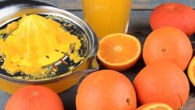 Mandarinas, naranjas, un vidrio de zumo de naranja y squezeer manual de la fruta cítrica en fondo de madera azul Naranjas cortada almacen de video
