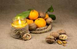 Mandarinas, nueces y una vela Fotos de archivo