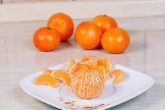 Mandarinas peladas en la placa Imagenes de archivo