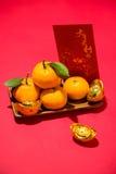 Mandarinas y Año Nuevo lunar con el ` de la Feliz Año Nuevo del ` del texto en el bolsillo rojo Concepto del día de fiesta de Tet Imagen de archivo libre de regalías