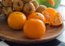 Mandarinas y fruta anaranjadas frescas en la placa de madera Imagen de archivo libre de regalías