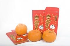 Mandarinas y paquete chino del rojo del Año Nuevo Fotos de archivo